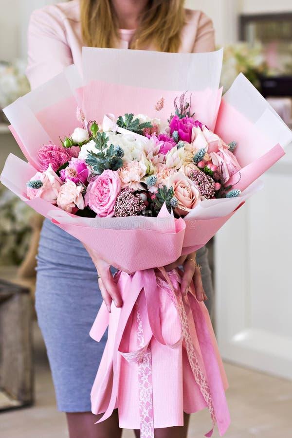 在桃红色包装纸的美丽的花束 玫瑰和其他精美美丽的花 图库摄影