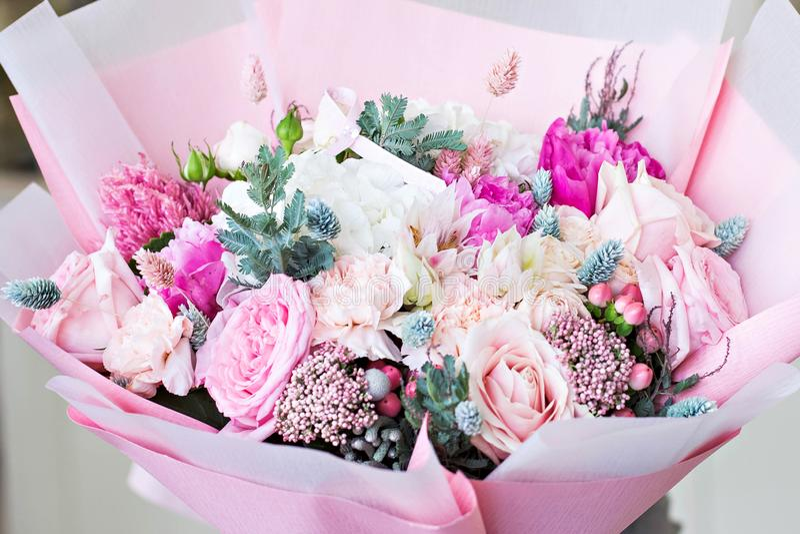 在桃红色包装纸的美丽的花束 玫瑰和其他精美美丽的花 免版税库存图片