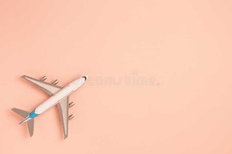 在桃红色背景的平的被放置的飞机 概念旅行 库存照片