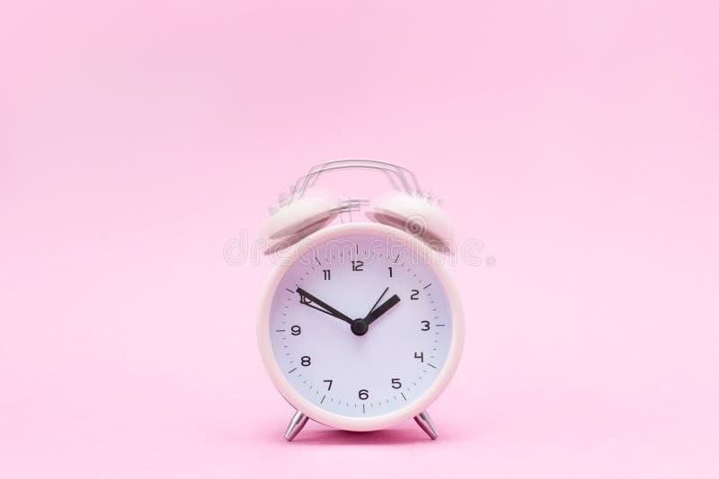 在桃红色背景的桃红色敲响的闹钟 免版税库存图片