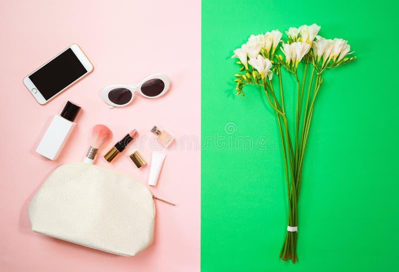 在桃红色背景的顶视图女性辅助部件化妆用品太阳镜在绿色背景的手机和花 日s华伦泰 免版税库存图片