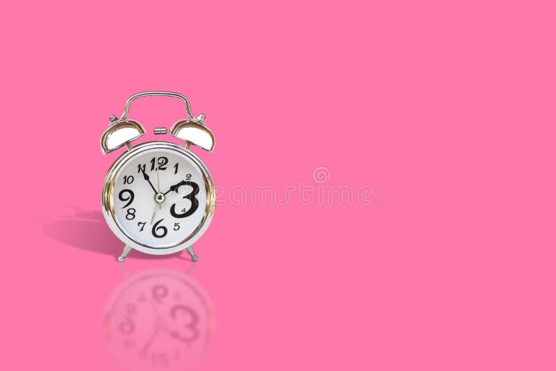 在桃红色背景隔绝的银色闹钟 库存照片