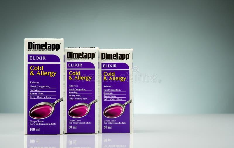 在梯度背景有量杯的和包装隔绝的琥珀色的瓶的Dimetapp不老长寿药 鼻解充血药 库存照片