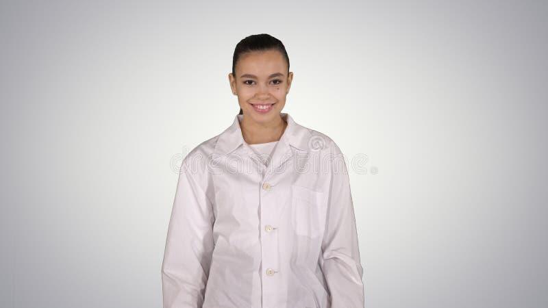在梯度背景的愉快的年轻女人医生舞蹈 库存照片