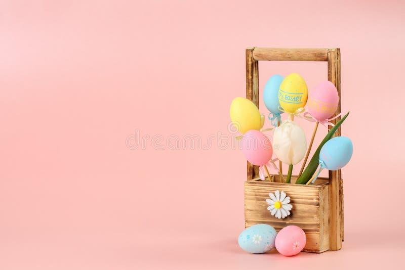 在棍子和白色郁金香的桃红色,黄色和蓝色被绘的鸡蛋在花的一个木篮子在桃红色背景 复活节概念, 库存照片