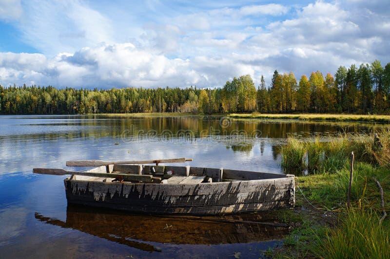 在森林湖的岸的木小船 免版税库存照片