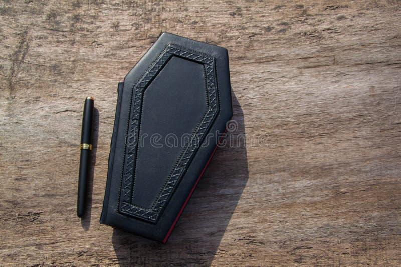 在棺材形状的皮革书,有对此的一支铅笔的 免版税库存照片