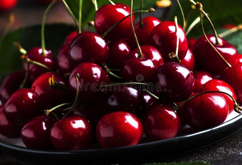 在棕色厨房用桌背景,静物画,选择聚焦的红色甜樱桃 库存照片