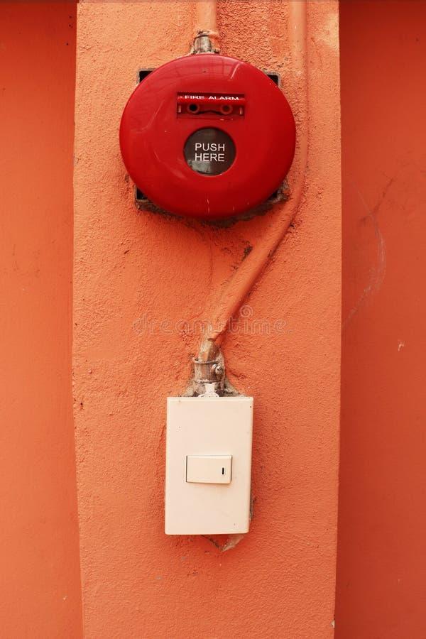在橙色墙壁上的红火警报 图库摄影