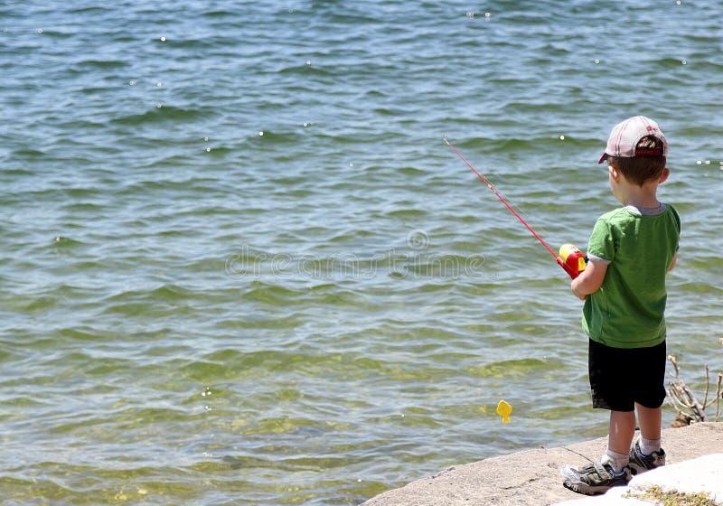 在水库的小男孩钓鱼在奥斯汀附近 库存照片