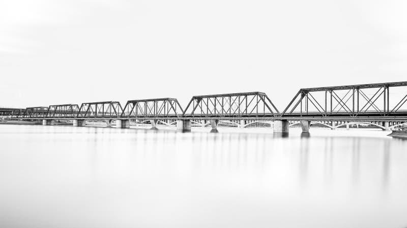在水的老铁火车桥梁 免版税图库摄影