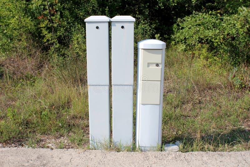 在沥青后院边缘登上的三个狭窄的高塑料电子箱子在与高草的被放弃的工业体系和 图库摄影
