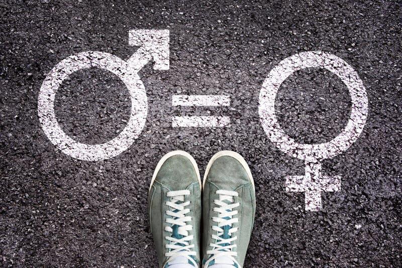 在沥青背景与性别标志,男女平等概念的运动鞋鞋子 免版税库存照片