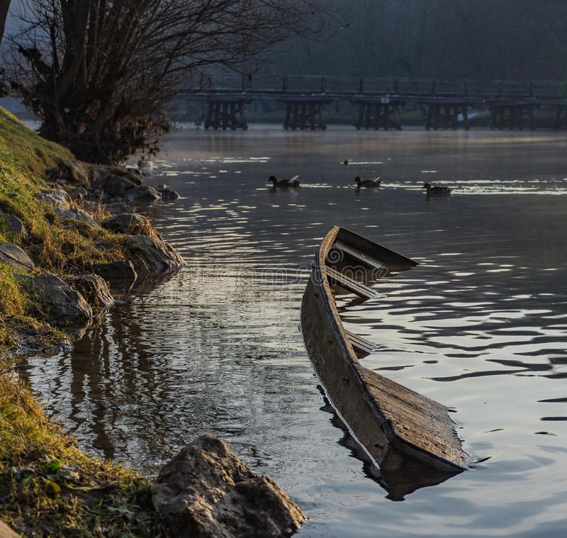 在河的海岸的凹下去的河船 库存照片
