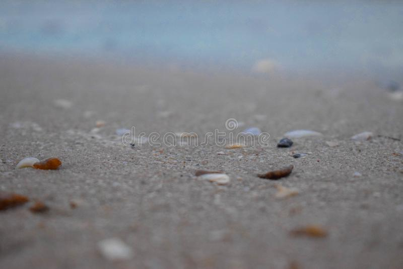 在沙子和小小卵石围拢的岩石,是在海前在海滩上升了 库存图片