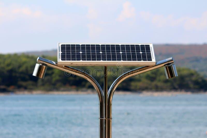 在海海滩的双重公开阵雨供给动力与在上面和森林的小太阳电池板用风平浪静在背景中盖了海岛 免版税库存图片