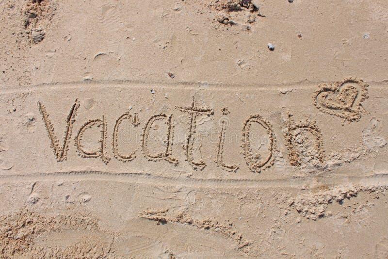 在海滩沙子的题字-假期 库存照片