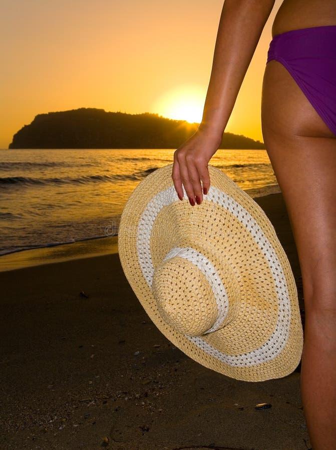 在海滩,一只典雅的女性手拿着一个帽子反对日落的背景 免版税库存照片