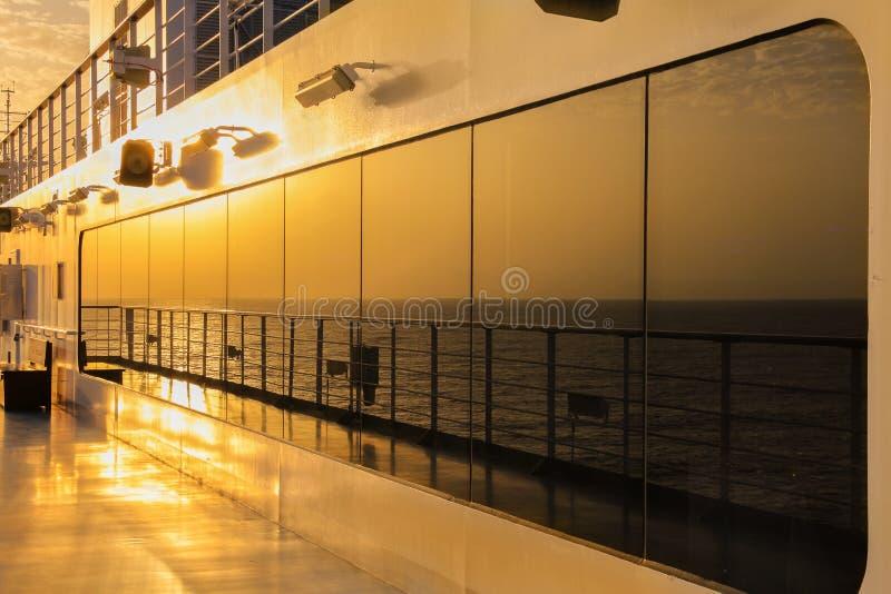 在海洋游轮的甲板的日落反射 免版税图库摄影