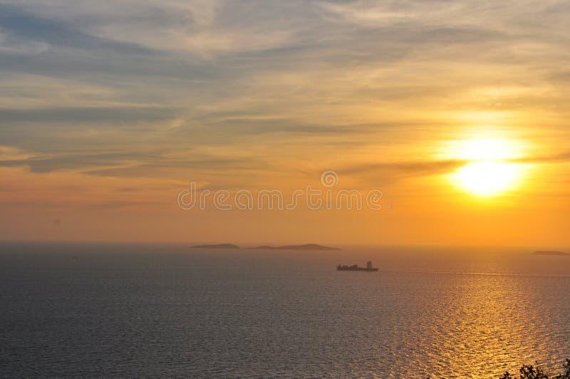 在海的日落有一条小船的在背景中 库存图片