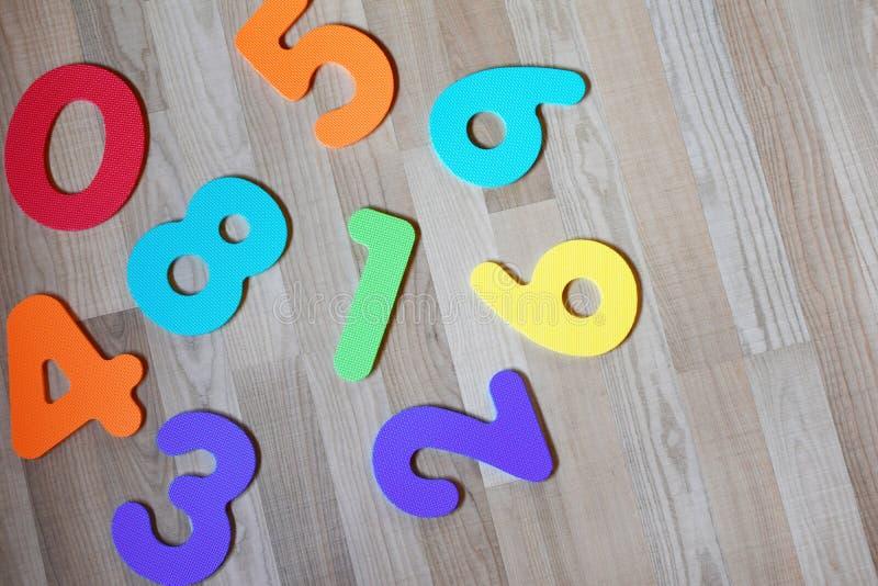 在浅褐色的木纹理层压制品的地板背景的五颜六色的数字 免版税库存照片