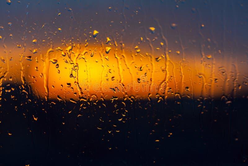 在湿窗口后的被弄脏的日落背景 库存图片