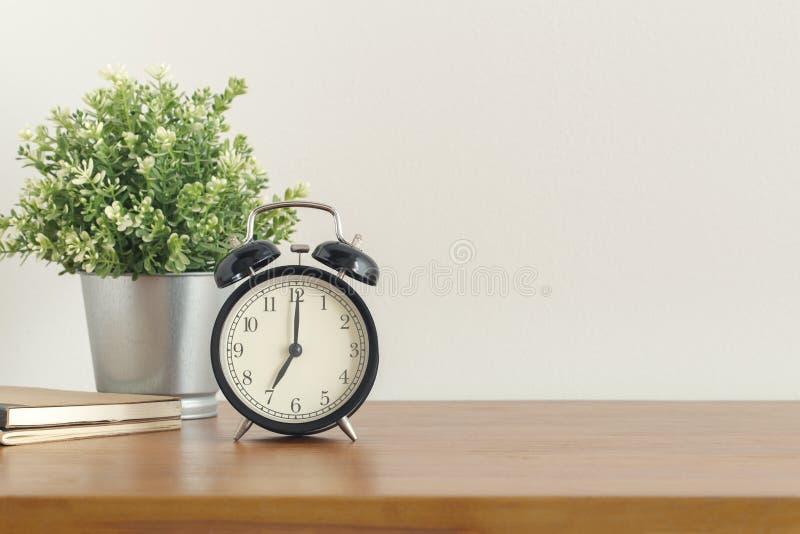 在木书桌上的黑闹钟在白色背景 免版税图库摄影
