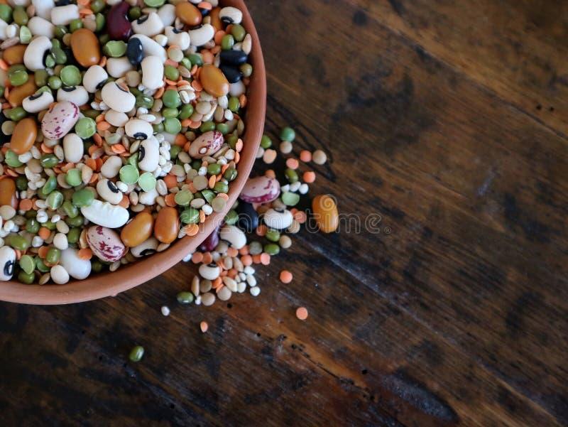 在木头的一个赤土陶器碗和谷物由豆品种做成,扁豆,azuki,大麦和拼写的五颜六色的混合物豆类 库存图片