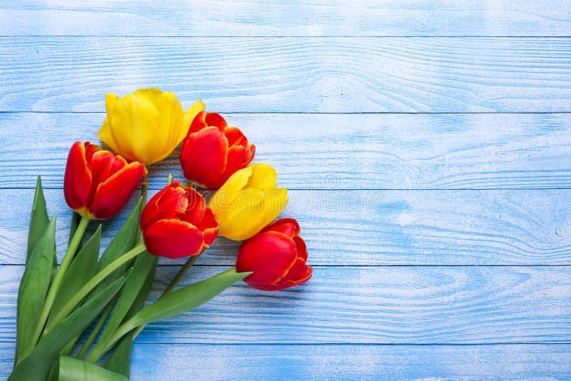 在木桌上的新鲜的五颜六色的郁金香花花束 免版税图库摄影