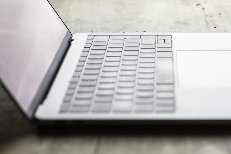 在木桌安置的膝上型计算机的模糊的照片 免版税库存图片