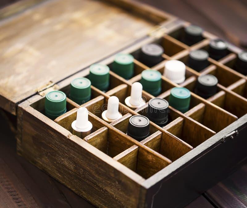 在木箱的芳香疗法精油 与精油瓶的草本替代医学在木箱,健康有机 免版税库存图片