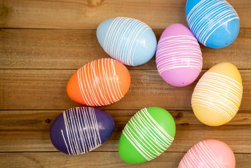 在木背景的五颜六色的淡色复活节彩蛋 Flatlay平展放置春天的背景 免版税库存照片