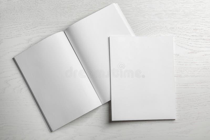 在木背景的开放和闭合的空白的小册子 免版税库存图片