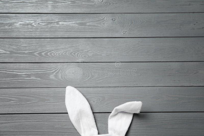 在木背景,顶视图的滑稽的复活节兔子耳朵 免版税库存照片