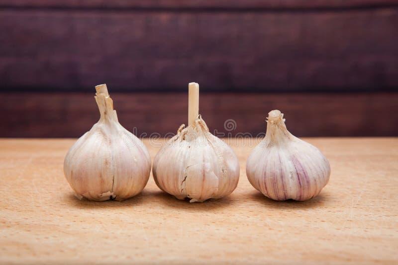 在木背景-在烹调和草药的香料的大蒜 图库摄影