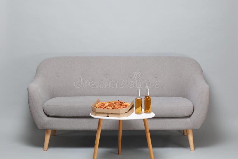 在木腿的现代灰色沙发,加奶咖啡桌用在纸板flatbox瓶的意大利比萨啤酒 库存图片