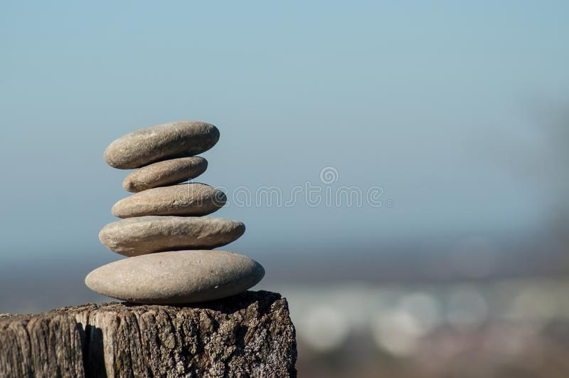 在木fenceon被弄脏的农村风景背景的石平衡 库存图片