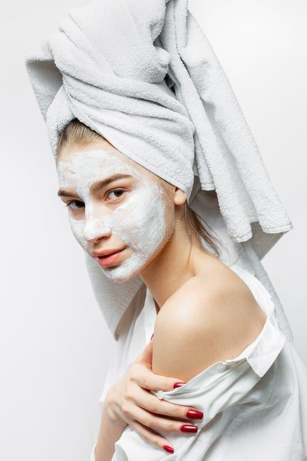 在有一块白色毛巾在她的头发和化妆面具的白色衣裳打扮的美丽的年轻女人在她的面孔拿着她 库存照片