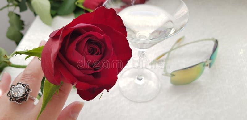 在戴着与白色大石头的女性手指的一朵红色玫瑰银色圆环 库存图片
