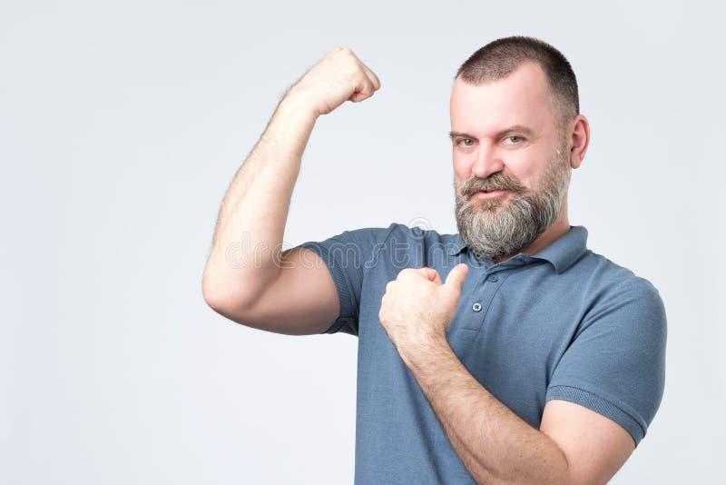 在显示胳膊肌肉的英俊的中年欧洲有胡子的人 免版税库存照片