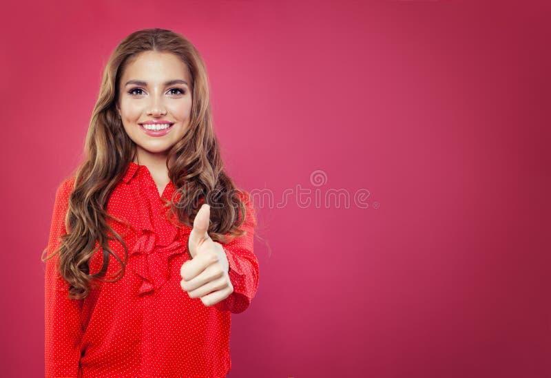 在明亮的桃红色横幅背景的年轻愉快的妇女陈列赞许 有赞许姿态的,正面情感微笑的女孩 库存照片