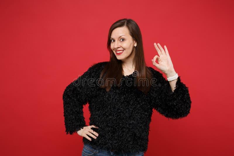 在明亮的红色墙壁上黑毛皮毛线衣身分的,显示好姿态隔绝的可爱的年轻女人画象  库存图片