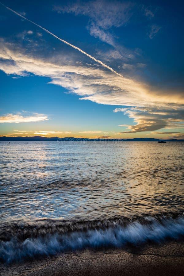 在日落期间,波浪在湖边海滩软软地碰撞在与黄色和白色云彩和一深天空蔚蓝的太浩湖 图库摄影