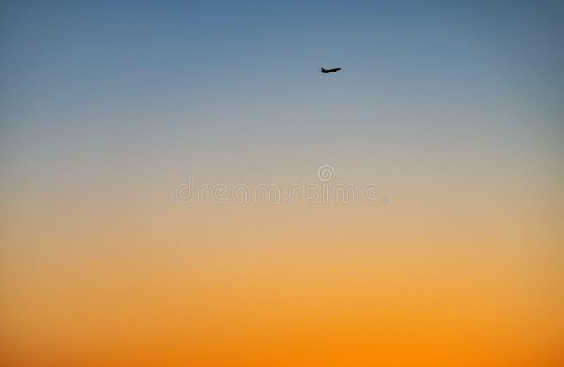 在日落的天空与飞机的剪影 免版税库存照片