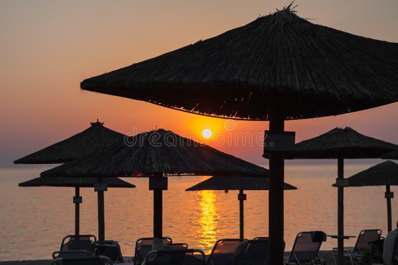 在日落的沙滩伞由海 库存图片