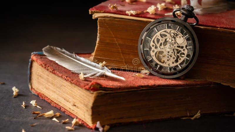 在旧书的绞的怀表与羽毛和干花瓣 免版税库存图片