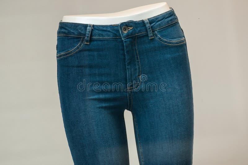 在时装模特的有弹性蓝色牛仔裤在妇女时尚商店陈列室里 库存照片