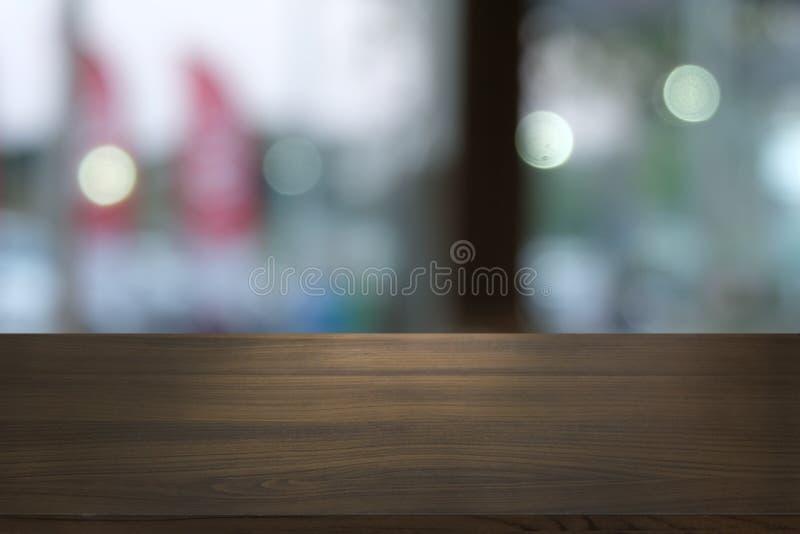 在摘要前面的空的黑暗的木桌弄脏了餐馆bokeh背景  库存图片