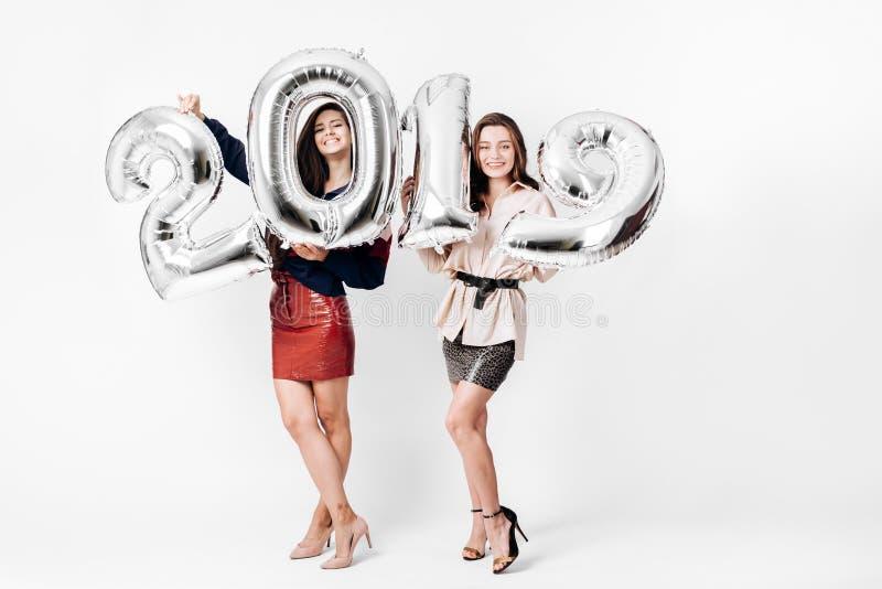 在打扮的两个迷人的女孩时髦的巧妙的衣裳拿着气球以在白色的第的形式2019年 库存图片