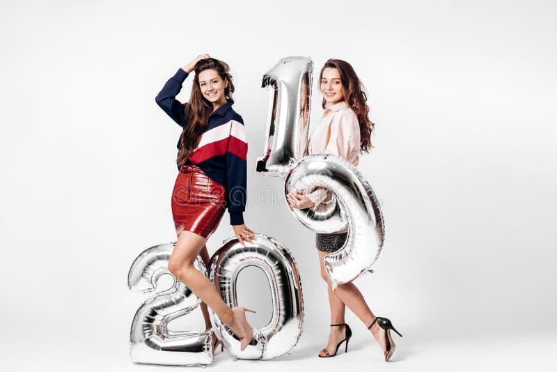 在打扮的两个迷人的女孩时髦的巧妙的衣裳拿着气球以在白色的第的形式2019年 图库摄影